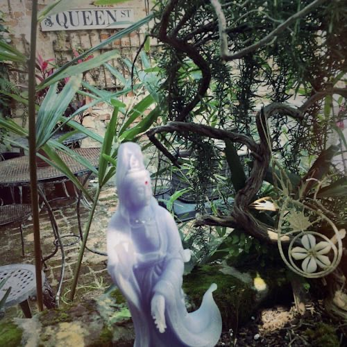 "Photo of Jenelle's Garden. In the garden is a statue of Quan Yen and a street sign that reads ""Queen Street."""
